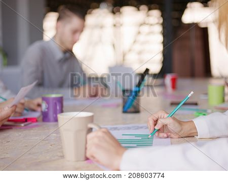 A girl with a coffee and pencil in the other hand looks at the company's work schedule.