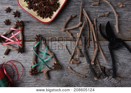 Top view of the equipment and supplies for making rustic Christmas decorations, including twigs, star anise, shears, and ribbon.