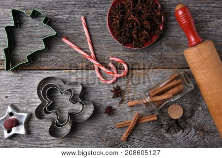 Overhead view of a holiday baking still life on a rustic kitchen table. Cookies Cutters, rolling pin, candy canes and spices laid out on the table.