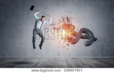 Young furious businessman crashing with hammer stone dollar symbol