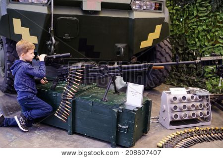 The Child Is Looking At A Large-caliber Machine Gun At An Exhibition