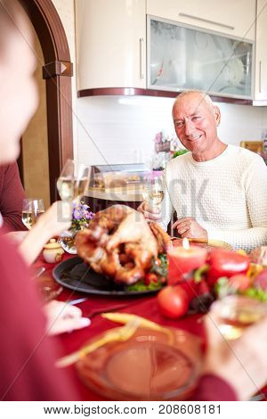 Happy family having dinner on the holiday table at home. Tasty baken chicken with vegetables on the table. Close-up of man. Food concept.
