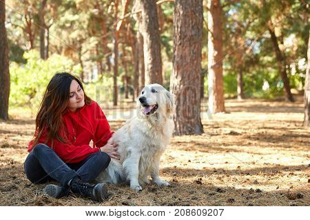Autumn forest, young girl is playing with her golden retriever outdoor. Submission. Friens and animals concept.