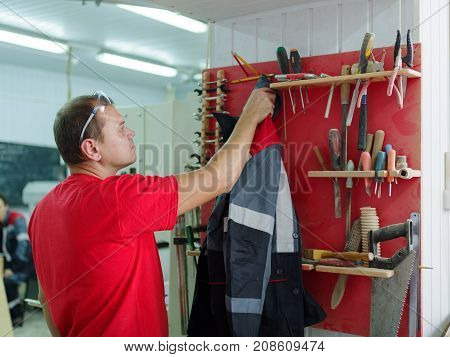 An employee in a red shirt, a mature man hanging a jacket in his working room