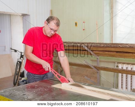 The carpenter, wearing glasses and his form, saws the timber of the wood on a circular saw and holds the beam with a special device in the working room