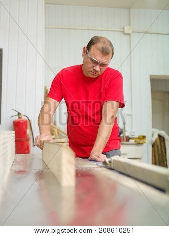 The joiner in the profile is leveled by the timber beam on a special machine close-up in the working room
