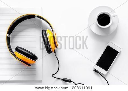 Worktable of composer today. Headphones, phone, music notes on white background top view.