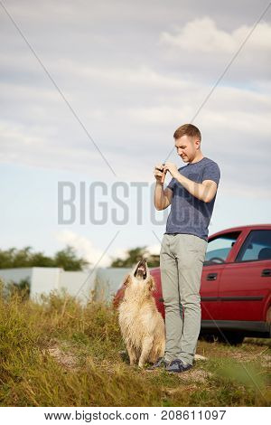 Golden retriver and owner playing near the river and having fun. Cutie pet and man enjoying life on the fresh air. Full lenght of man with labrador.