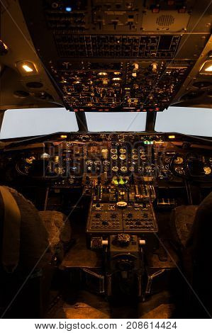 Old commercial aircraft cockpit with gauges glowing in the dark