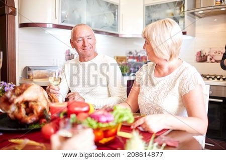 Happy family having dinner on the holiday table at home. Tasty baken chicken with vegetables on the table. Close-up of grandparents. Food concept.
