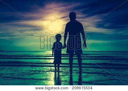 Silhouette back view of loving child holding hands her father standing in the sea. Family enjoying and relaxing on beach with full moon on sky background. Cross process. The moon taken with my own camera.