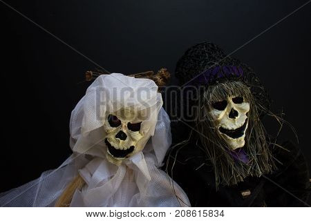 Close up of skeleton bride and groom in white and black against a black background.