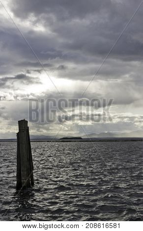 Vertical of three weathered pier corner posts rising out of Burlington Bay, Vermont with a sailboat anchored offshore from the land in the distance on a cloudy gray late afternoon day in October.
