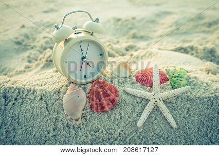 Clock and starfish on the sea white sand.