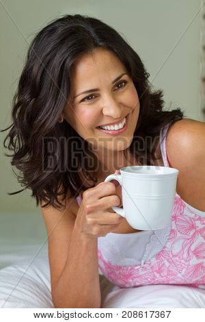 Beautiful mature hispanic woman lying in a bed.