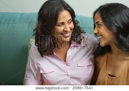 Mother talking and laughing with her teenage daughter.