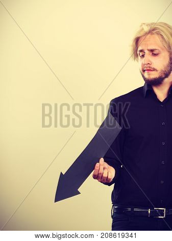 Man Holding Black Arrow Pointing Left Down