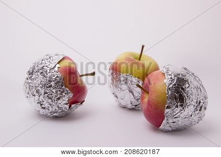 Several red and yellow ripe and juicy apples wrapped in foil on a white background