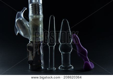 Rubber vibrator for sexual pleasure and transparent glass anal plug on a black background