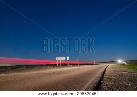 Rural asphalt road in twilight with the headlights of passing cars on it at slow shutter speeds