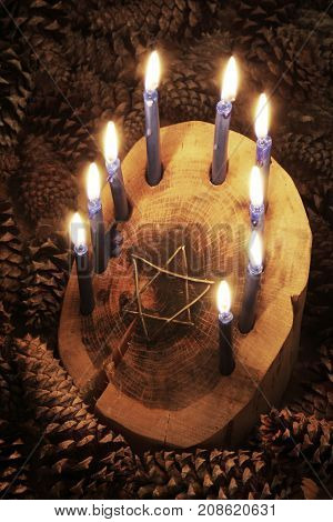 Crafted rustic wood log menorah surrounded by pine cones with inset Star of David, candles lighted