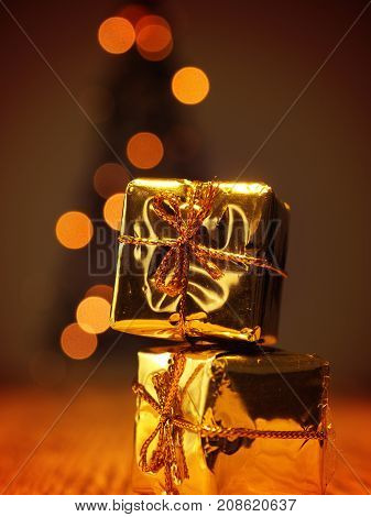 Two golden Christmas gift boxes with a blurred Christmas tree background