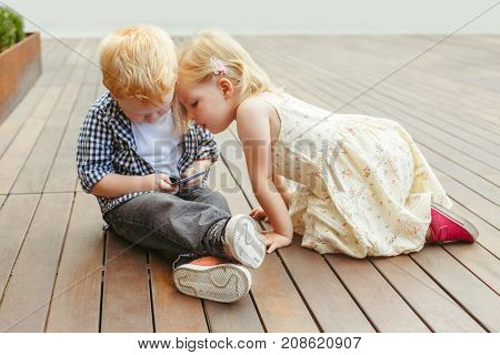 Two cute adorable white Caucasian toddlers boy and girl sitting together and playing games on cell mobile phone digital tablet. Candid lifestyle early development. New technology generation.