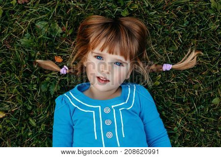 Closeup portrait of cute adorable little red-haired Caucasian girl child in blue dress lying in field meadow park outside looking in camera. Happy lifestyle childhood concept