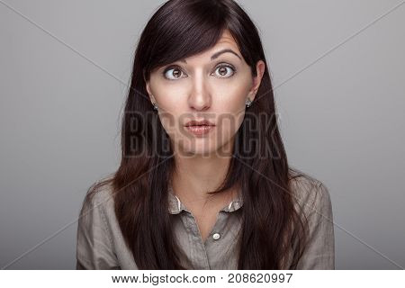 Closeup portrait of beautiful young middle age brunette Caucasian woman with brown eyes with funny emotional face expression. Girl female with long dark hair looking surprised hilarious