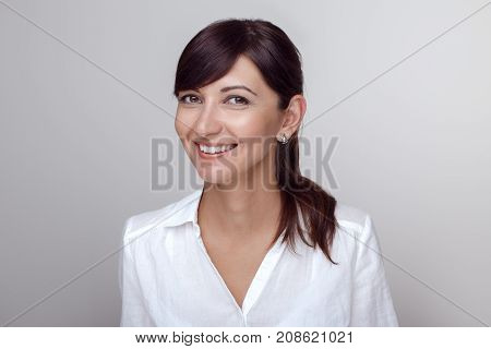 Closeup portrait of beautiful smiling young middle age brunette Caucasian woman with brown eyes looking in camera. Girl female with long dark hair in white office shirt. Studio beauty shot.
