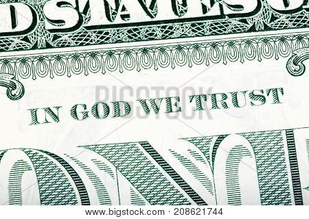Dollar macro, stacked close-up detail photo. In God we trust sentence visible. One-dollar bill fragment. U.S. Treasury.