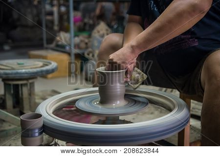 Craftsman creating ceramic pottery by using electrical motor rotation machine to form the figure of pottery