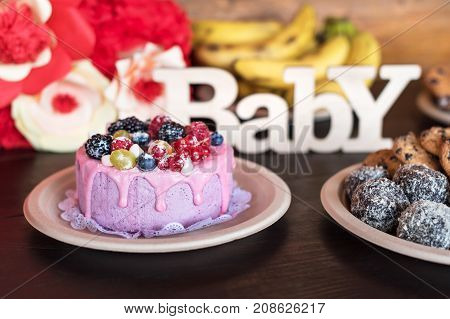 Birthday cake and muffins with wooden greeting sign on dark background. Wooden sing with letters Baby and holiday sweets