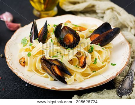 Seafood Fettuccine Pasta With Mussels Over Black Background. Mediterranean Delicacy Food.