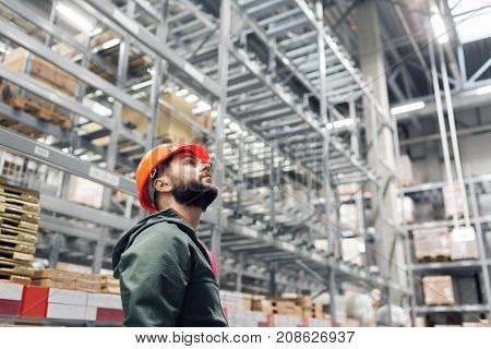 wholesale, logistic, people and export concept - manager or supervisor with tablet at warehouse. looking thoughtfully at the top