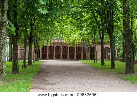 Alley of old deciduous trees leading to ancient building with columns. Palace Johannisburg town Aschaffenburg Germany. Tourist attraction tourists destination point
