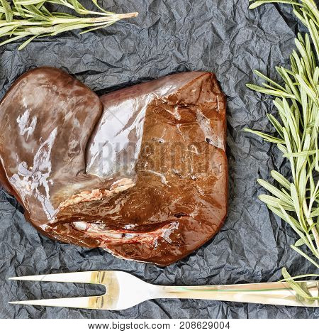 Healthy Fod Raw Liver With Rosemary On A Black Background