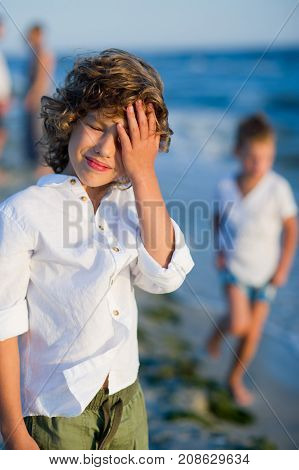 Portrait of boy of 10-11 years against the background of the rough sea. He covers eyes with a palm from the blinding sun.