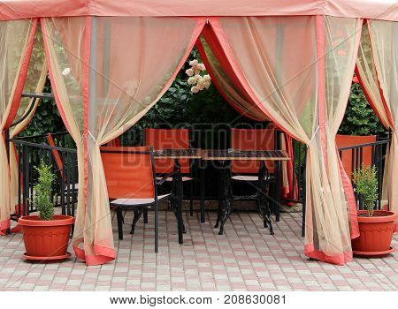 summer tent from the sun and tables for relaxing outdoors on a background of rose bushes.