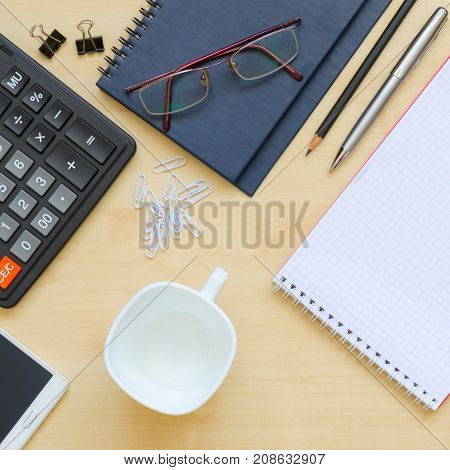 Top view office desk with notepads phone paper for notes calculator coffee cup and glasses. Copy space background top view flat lay overhead