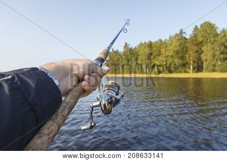 Fishing on a lake. Fishing rod with a reel in hand. Vew of the shore.