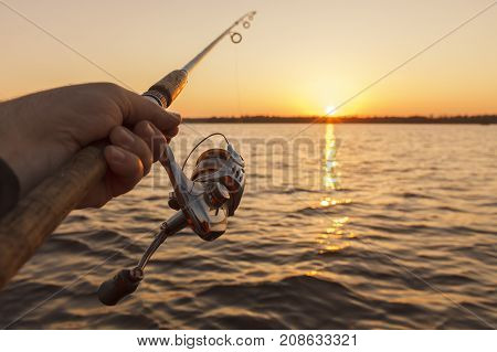 fishing rod in hand on sunset background.solar path.
