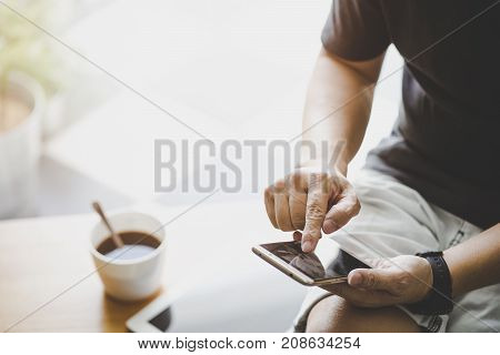 Smartphone in young man hand with digital tablet and coffee .