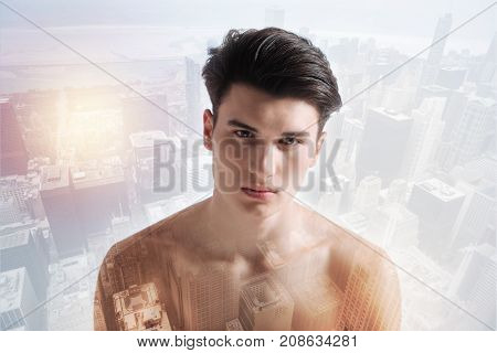 Feeling embarrassed. Upset naked boy having sadness in his eyes while standing against urban background