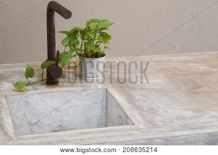 Morden black faucet and kitchen room sink with cement countertops and green grass .