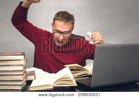 Young student man becomes hysterical from studying. Office worker overworked at work. Mad student sitting at the table and throws the piece of paper and prevents to lead a lesson. Bad day.