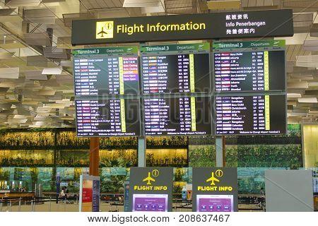 Singapore - Jun 27 2017 : Flights information board and machine at Changi airport terminal 3