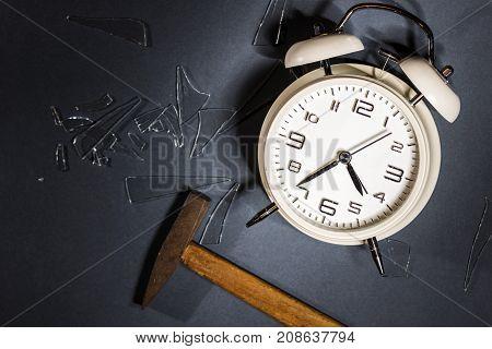White Crashed Alarm Clock, Shards Of Glass And Hammer On Grey Background.