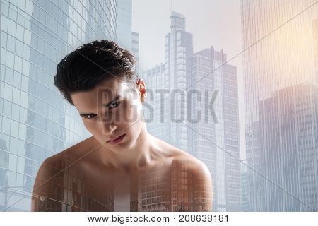 Away from people. Close up of young handsome model expressing coldness in his eyes while standing against city background