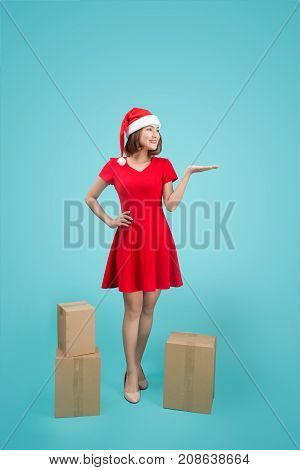 Full-body Of Attractive Cheerful Asian Girl In Santa's Hat Showing With Her Hand At Copy Space And H
